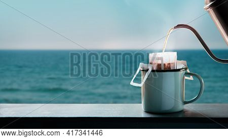 Dripping Coffee By The Sea Side At Morning. Making Hot Drink By Pouring Hot Water From Kettle Into A