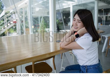 Young Happy Woman Smile Sitting In Cafe Wearing Smart Watch. Portrait Of Asian Young Female In Casua