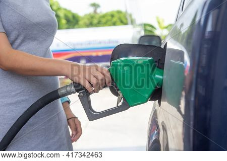 Blue Car At Gas Station Filled With Fuel. Closeup Pregnant Woman Hand Pumping Gasoline Fuel In Car A