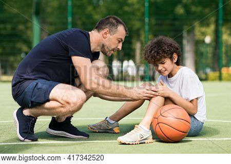 Teacher Helping Boy With Knee Trauma After Playing Basketball