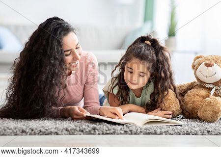 Children Development Concept. Loving Young Mom Reading Book To Her Little Daughter