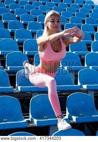 Flexible Woman Stretching On Stadium Seats In Sportswear, Flexibility