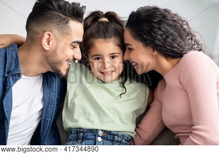 Parental Love. Happy Arabic Parents Cuddling Their Cute Little Daughter At Home