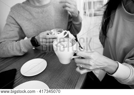 Young Couple Drinking Hot Beverages. Close Up Woman And Man Sitting In Cafe, Holding Warm Cups Of Co