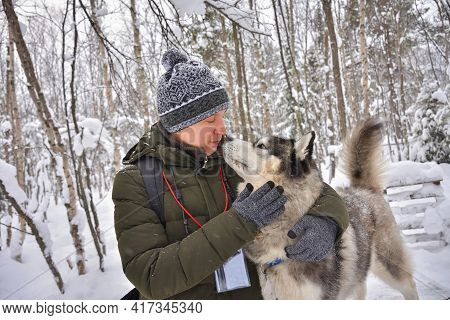 A Man Hugs A Husky In A Snowy Forest Close-up