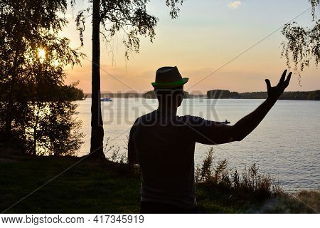 Silhouette Of A Man With His Hand Raised Against The Setting Sun