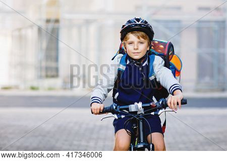 Schoolkid Boy In Safety Helmet Riding With Bike In The City With Backpack. Happy Child In Colorful C