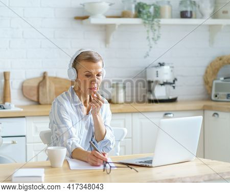 Modern Focused Middle Aged Woman Wearing Headphones Making Some Notes While Studying Online On Lapto