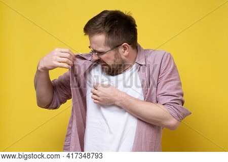 Disgruntled Man With Glasses And Casual Clothes Sniffs His Armpits, Annoyed By The Problem Of Sweat