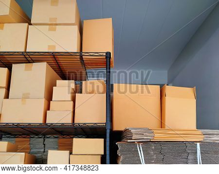 Various Sizes Of Carton Boxes On Shelf Display With Stack Of Folding Cardboard Boxes For Sale At Sto