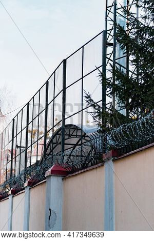 Tall Concrete Fence With Barbed Wire And Another Mesh Fence Above. Protection. Fair. Security. Trees