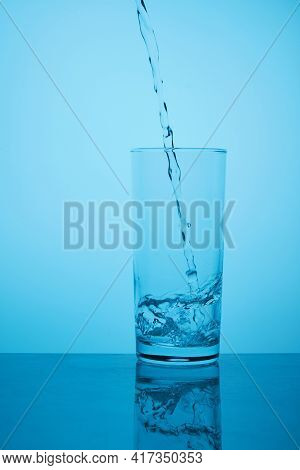 Glass Of Pure Still Water. Thirst Quenching. Pure Still Water Pours From Bottle To Glass Against Blu