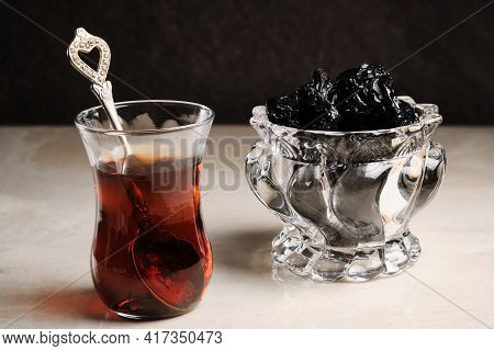 Turkish Tea In Traditional Tea Glass And Dried Prunes At Bright Table Against Dark Background