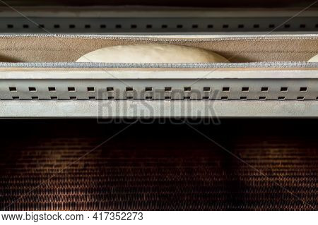 Production Of Bakery Products At Industrial Factory. Raw Dough At Bakery Equipment.