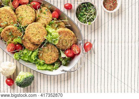 Metal Dish With Vegan Vegetable Burgers And Salad