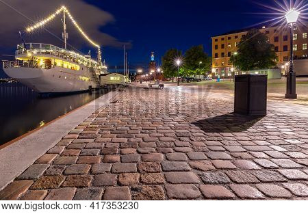 Stockholm. Old City Embankment With Glowing Lanterns At Sunset.