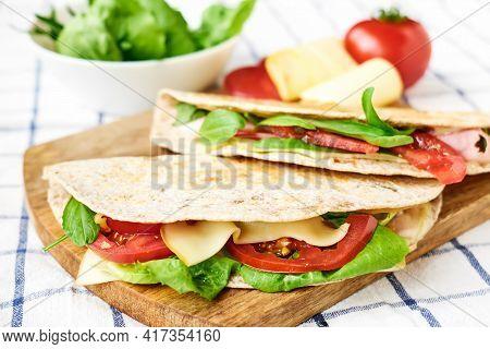 Piadina Romagnola With Mozzarella Cheese, Tomatoes, Ham And Rocket Salad On A Cutting Board. Italian