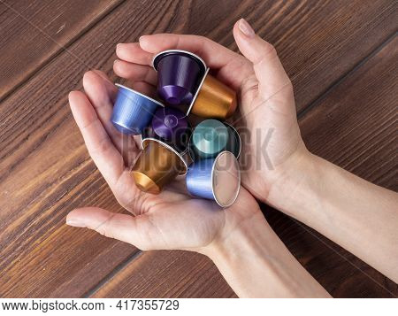 In The Women's Open Palms Are Colorful Capsules With Coffee. Wooden Background, Coffee Machine Capsu