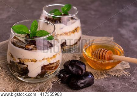 Yogurt With Date, Granola And Honey In Glasses On A Gray Background.