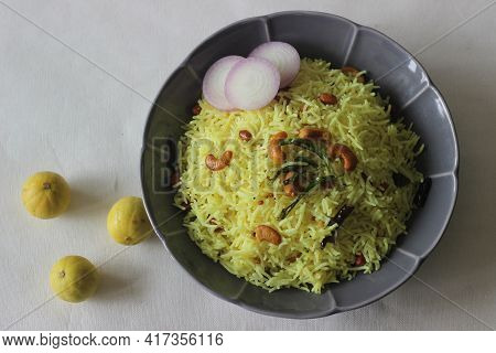 Lemon Rice Made By Seasoning Cooked Rice With Spices, Leaves, Turmeric And Lime Juice.