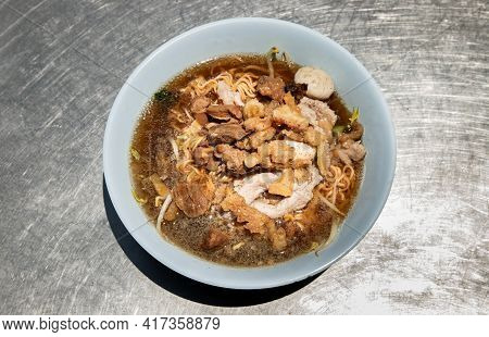 Instant Noodles In Braised Pork Soup With Pork Balls And Fatty Pork Rinds In White Bowl. Thai Food,