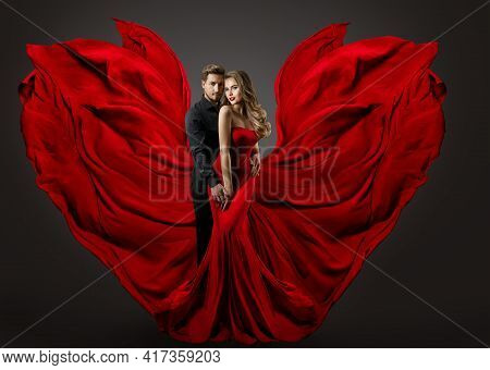 Fashion Couple In Love. Woman In Fantasy Long Red Gown And Handsome Man. Flying Silk Fabric As Wings