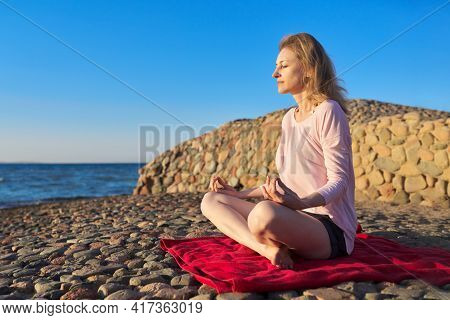 Beautiful Mature Woman Sitting In Lotus Position Meditating On Seashore At Sunset