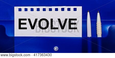 On A Blue Background, White Pens And A Sheet Of Paper With The Text Evolve