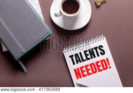 On A Brown Background, Diaries, A White Cup Of Coffee And A Notebook With The Text Talents Needed.