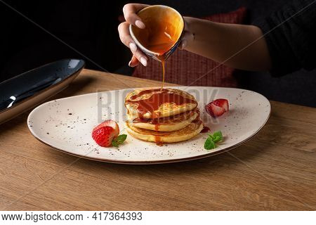 Stack Of Pancakes With Of Strawberry Slices, Pour Over With Caramel Syrup.