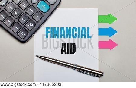 On A Light Gray Background, A Calculator, A White Sheet With The Text Financial Aid, A Pen And Brigh