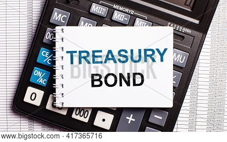 On The Table Are Reports, A Calculator And A Card With The Words Treasury Bond On It. Business Conce