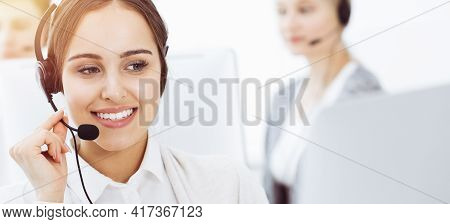 Call Center In Sunny Office. Group Of Diverse Operators At Work. Beautiful Woman In Headset Communic