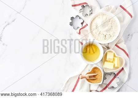 Baking Background With Flour, Eggs, Kitchen Tools, Utensils And Cookie Molds On White Marble Table.
