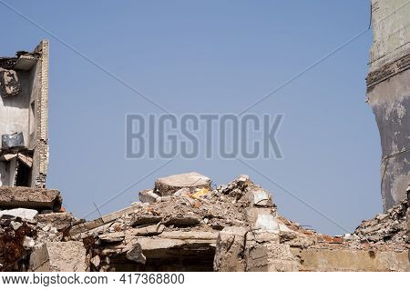 A Pile Of Construction Debris On A Ruined Foundation Against A Blue Cloudless Sky And The Remains Of