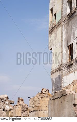 The Remains Of A Building Wall With Large Foundation Piles In The Foreground Against The Blue Sky. B