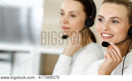 Blond Female Customer Service Representative And Her Colleague Are Consulting Clients Online Using H