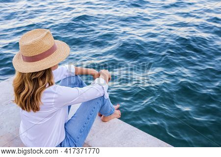 High Angle Shot Of Woman Weairng Straw Hat And Casual Clothes While Sitting On Seaside And Looking A