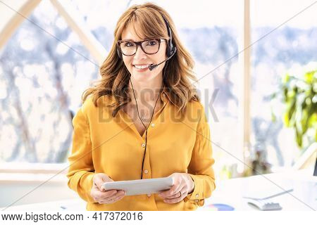 Mature Businesswoman In Headset Speaking By Conference Call And Holding Digital Tablet In Her Hand W