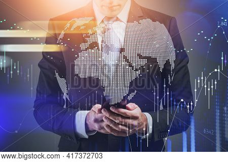 Front View Businessman Who Checking Stock Market Rates In Smartphone. Hologram Charts. Business And