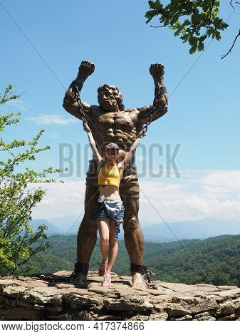 Russia, Sochi 12.07.2020. A Girl Poses Near A Statue Of Prometheus Holding On To His Chains. Statue