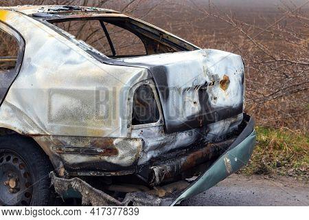 Burned Car After An Accident On The Asphalt Road. Close-up, Fragment. Arson Of A Car, Criminal Showd
