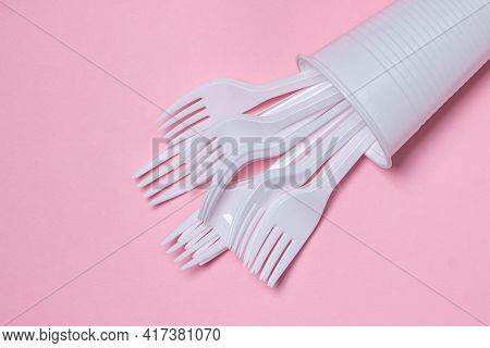 Plastic Dishes On A Pink Background. Plastic Forks In A Plastic Cup. Disposable Tableware. Plastic P