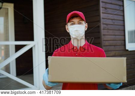 Portrait Of Deliverer Wearing Safety Mask Holding A Box. Service In Quarantine Coronavirus Covid-19