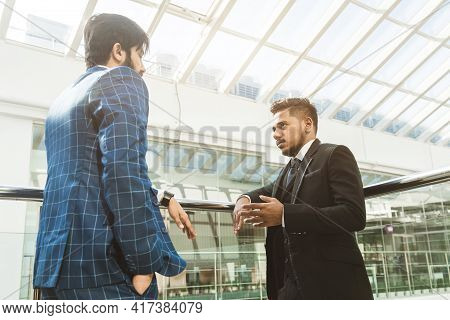 Young Business People Are Standing And Talking On The Background Of Glass Offices. Corporate Busines