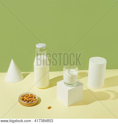 Glass With Vegan Milk From Almond Nuts With A Bottle And White Geometric Figures On Sunlit Backgroun