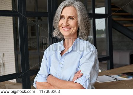 Smiling Adult Middle Aged Business Woman Standing At Table Posing In Home Office, Arms Crossed. Port