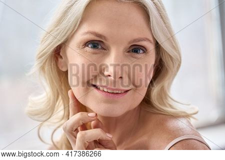 Adult Senior Older Woman Touching Perfect Soft Face Skin With Hand. Portrait Of Mid Age 50 Years Old