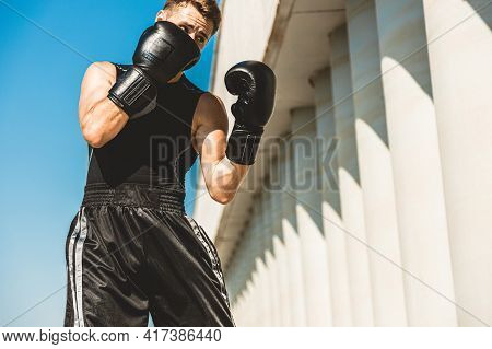 Man Exercising And Fighting In Outside, Boxer In Gloves. Male Boxer Portrait