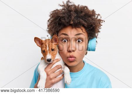 Close Up Shot Of Afro American Female Dog Owner Carries Pedigree Puppy Keeps Lips Folded Looks Shock